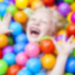 Blond Girl Child Having Fun Playing in Colored Balls